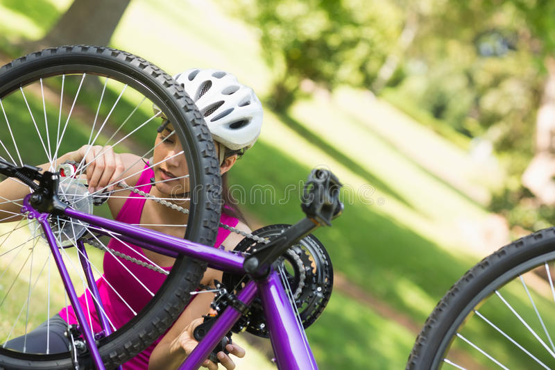 Frau, die versucht, Kette auf Mountainbike im Park zu reparieren lizenzfreies stockfoto