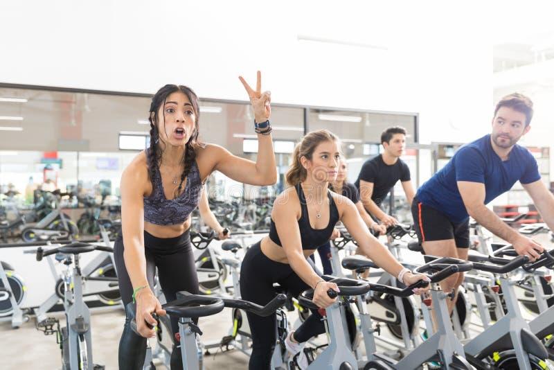Frau, die Victory While Exercising On Spinning-Fahrrad in der Turnhalle gestikuliert lizenzfreie stockbilder