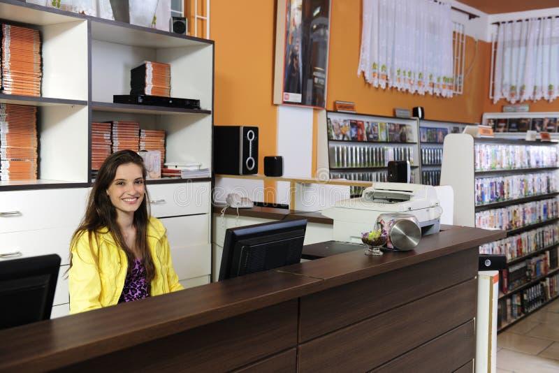Frau, die am video Mietspeicher arbeitet lizenzfreie stockbilder