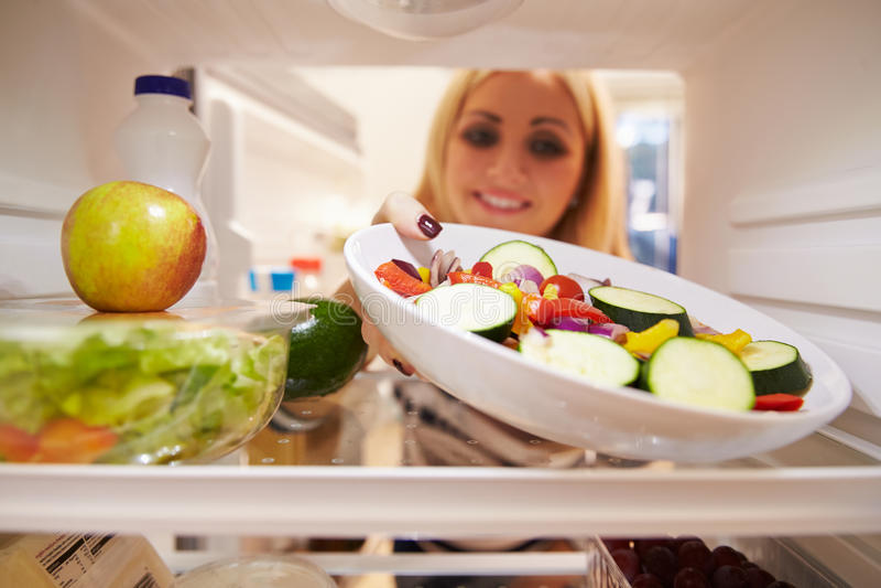 Frau, die voll inneren Kühlschrank des Lebensmittels schaut und Salat wählt stockfotos
