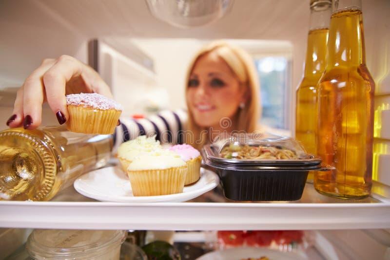 Frau, die voll inneren Kühlschrank ungesunden Foodï-¿ ½ schaut lizenzfreie stockfotos