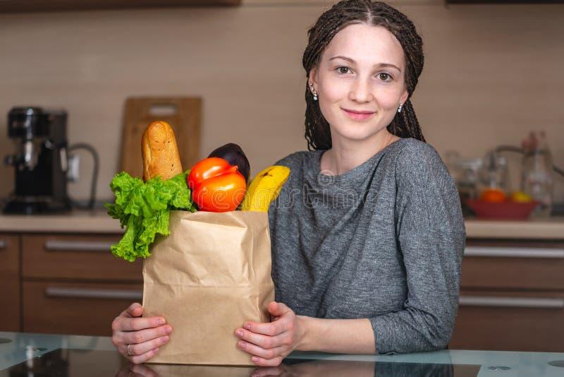 Frau, die volle Papiertüte mit Produkten auf dem Hintergrund der Küche hält Neues biologisches Lebensmittel für eine Vollkost lizenzfreie stockfotos