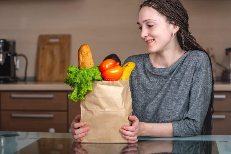 Frau, die volle Papiertüte mit Produkten auf dem Hintergrund der Küche hält Neues biologisches Lebensmittel für eine Vollkost stockfotografie