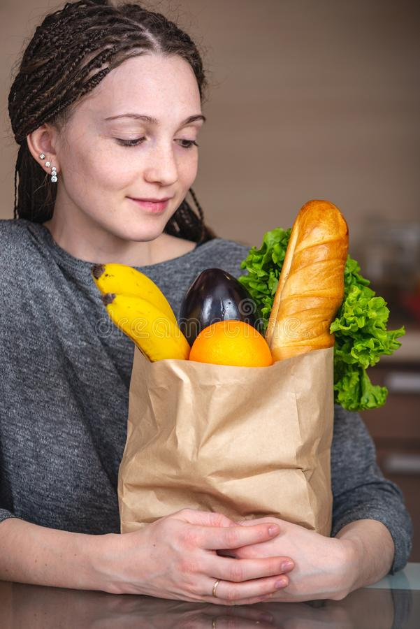 Frau, die volle Papiertüte mit Produkten in den Händen auf dem Hintergrund der Küche hält Gesundes und neues biologisches Leb lizenzfreies stockbild