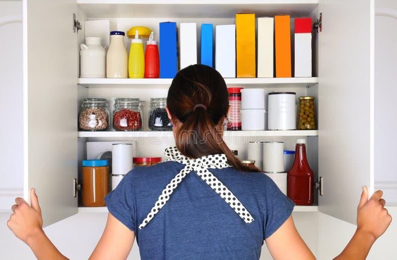 Frau, die vollen Speiseschrank öffnet lizenzfreies stockbild