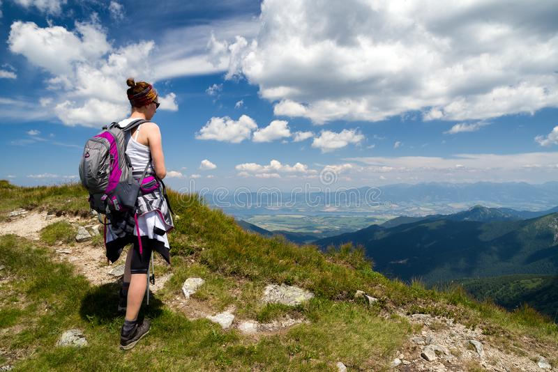Frau, die vom Hügel auf schöner Landschaft schaut lizenzfreie stockfotos