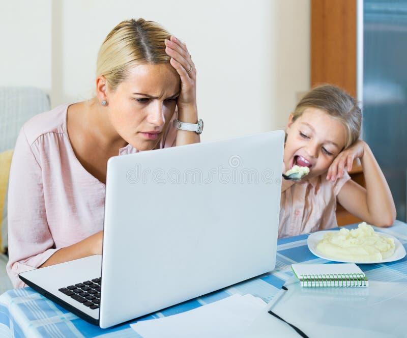Frau, die vom Haus, kleine Tochter bittet um Aufmerksamkeit arbeitet lizenzfreie stockbilder