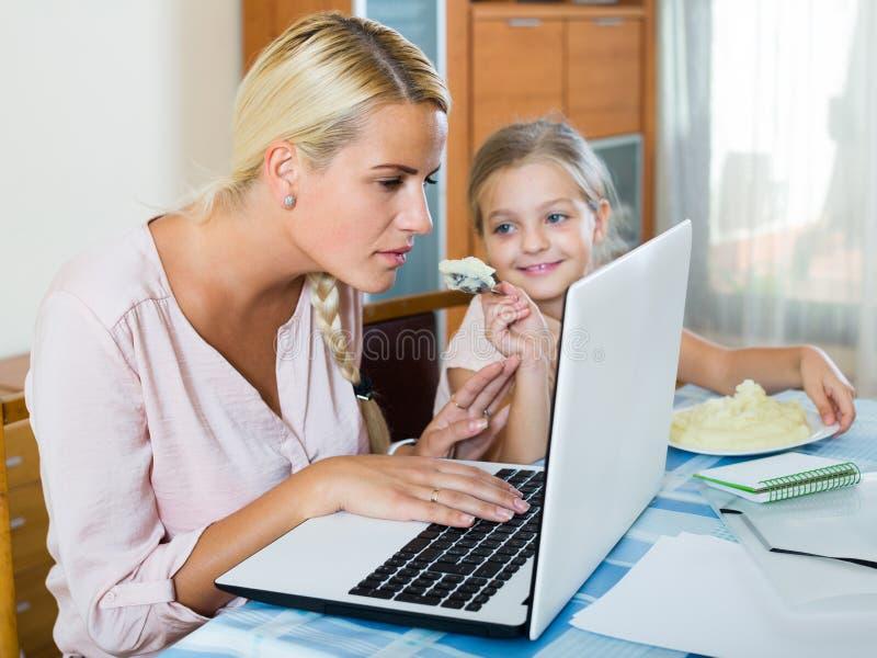 Frau, die vom Haus, kleine Tochter bittet um Aufmerksamkeit arbeitet stockfotos
