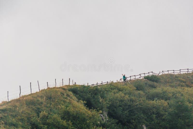Frau, die von einem Berg wellenartig bewegt stockfoto