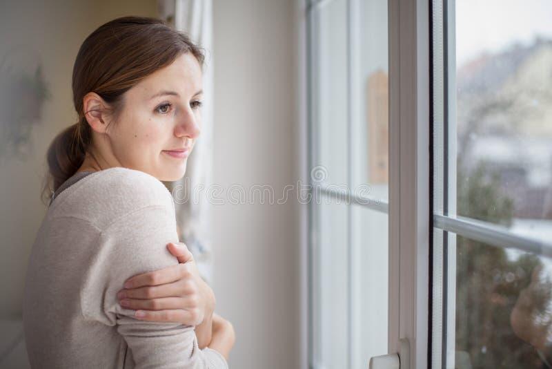 Frau, die von einem Fenster ihres Hauses schaut stockbild