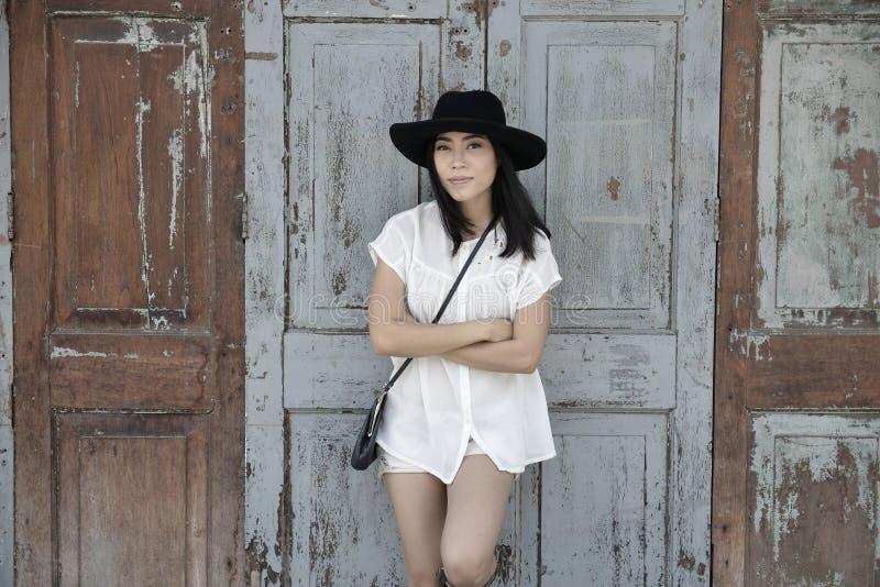 Frau, die vor altem Haus mit Retro- Farbfilter steht stockfotos