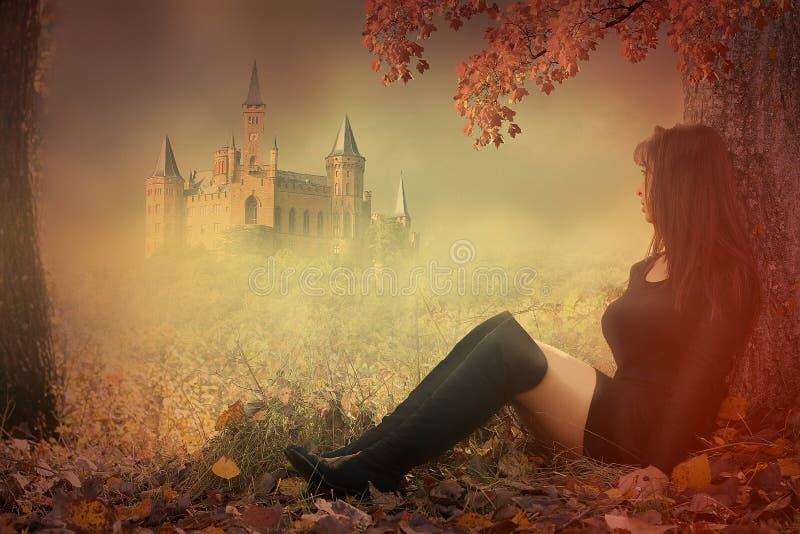 Frau, die vor einem Schloss sitzt stockfotografie