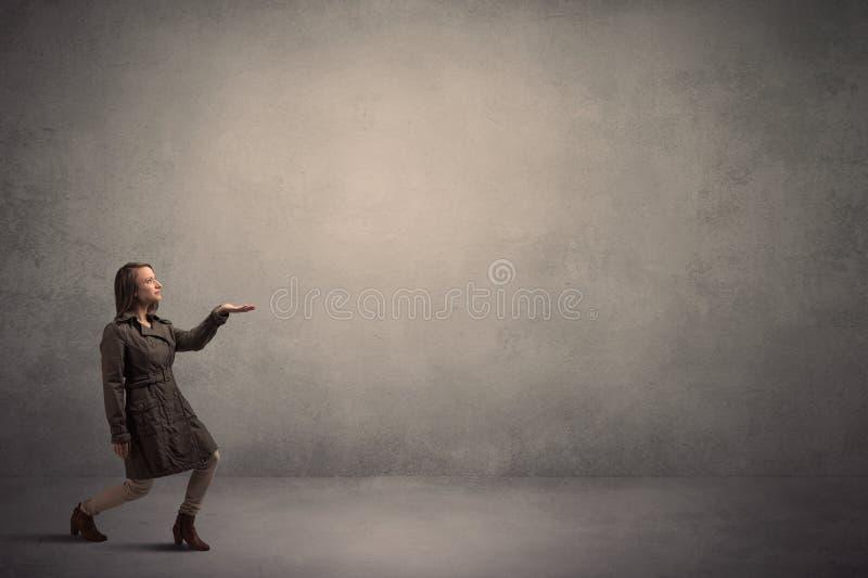 Frau, die vor einer leeren Wand steht stockbild