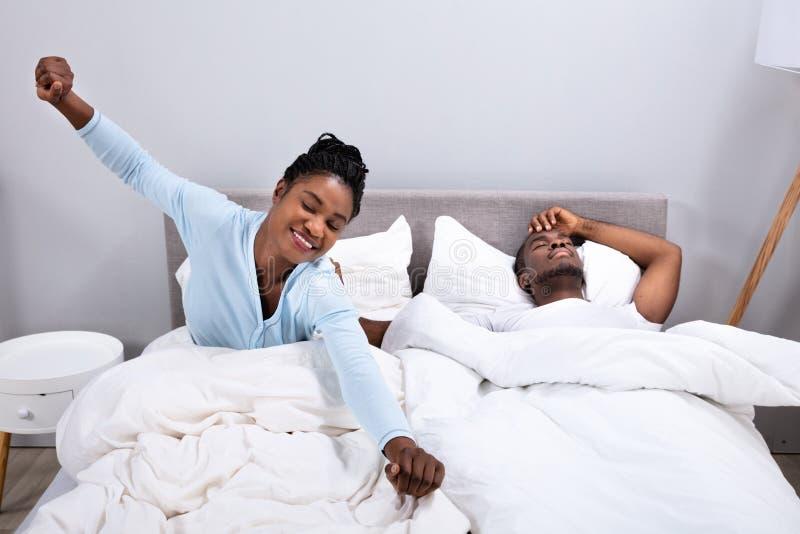 Frau, die w?hrend ihr Ehemann liegt auf Bett ausdehnt lizenzfreie stockfotos