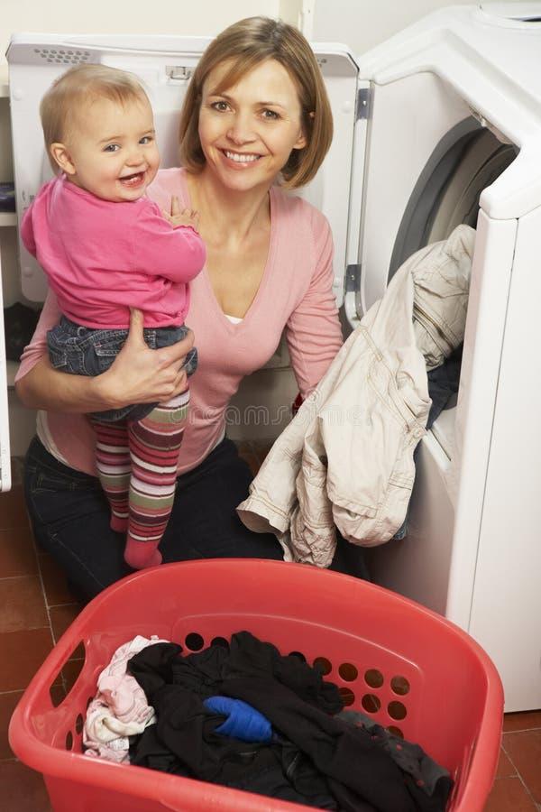 Frau, die Wäscherei tut und Tochter anhält lizenzfreie stockfotos