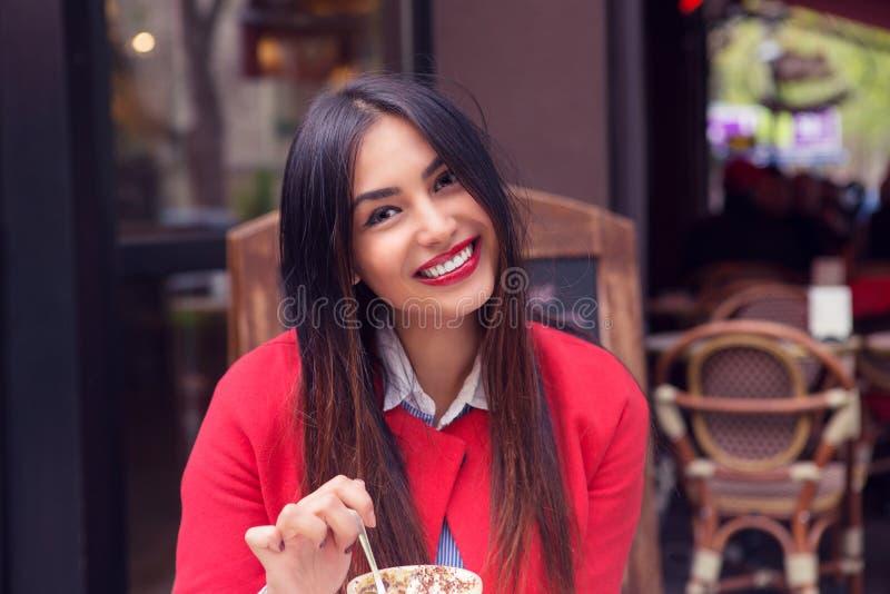 Frau, die Wüste in einem französischen Restaurant essend lächelt lizenzfreies stockfoto
