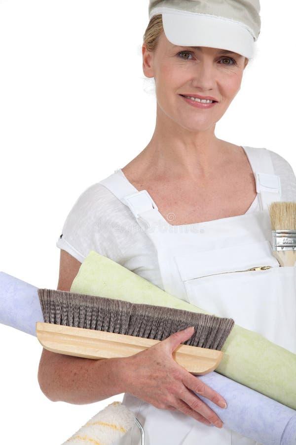 Frau, die wallpaper sich vorbereitet stockfoto