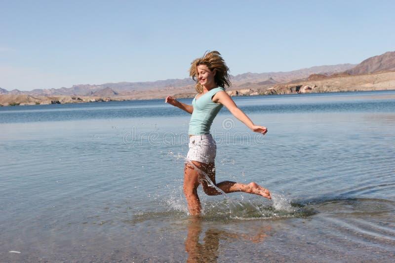 Frau, die in Wasser läuft stockfoto