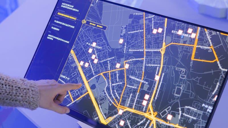 Frau, die wechselwirkende Anzeige des Bildschirm- an der modernen Technologieausstellung verwendet stockfotos