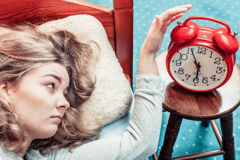 Frau, die Wecker am Morgen abstellend aufwacht stockfoto