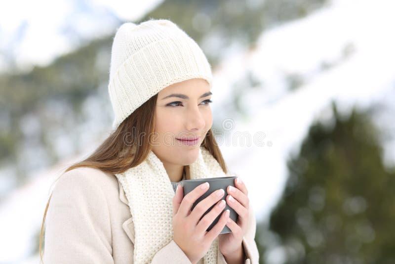 Frau, die wegholding eine Kaffeetasse im Winter schaut stockbilder