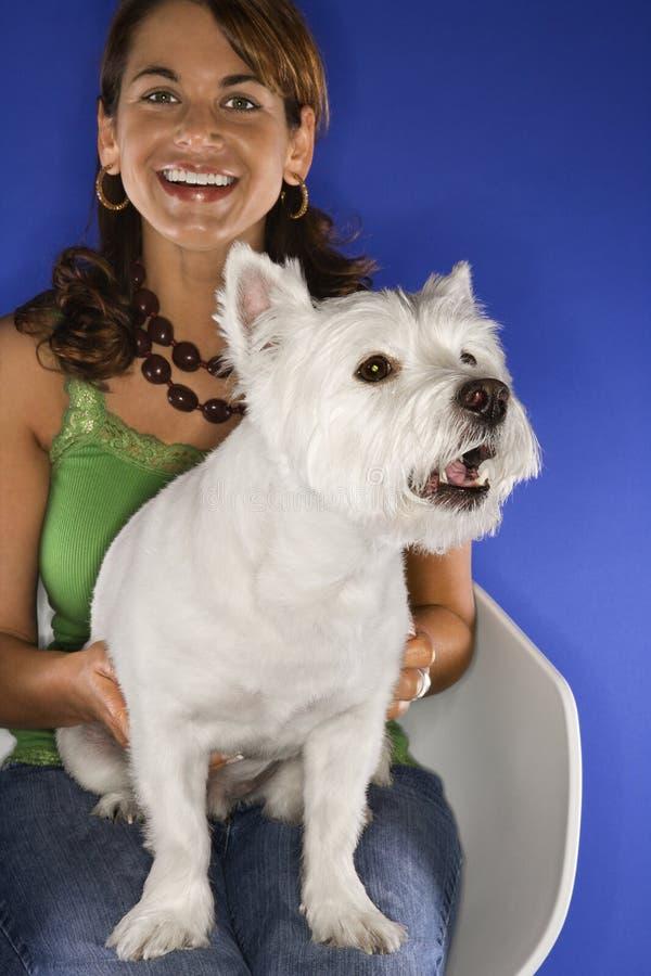 Frau, die weißen Terrier anhält. stockfoto