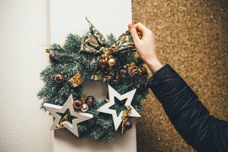 Frau, die Weihnachtskranz auf der äußeren Wand vereinbart lizenzfreie stockfotografie