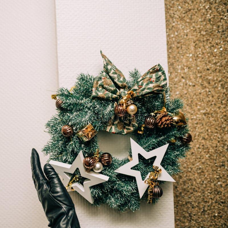 Frau, die Weihnachtskranz auf der äußeren Wand vereinbart lizenzfreies stockfoto