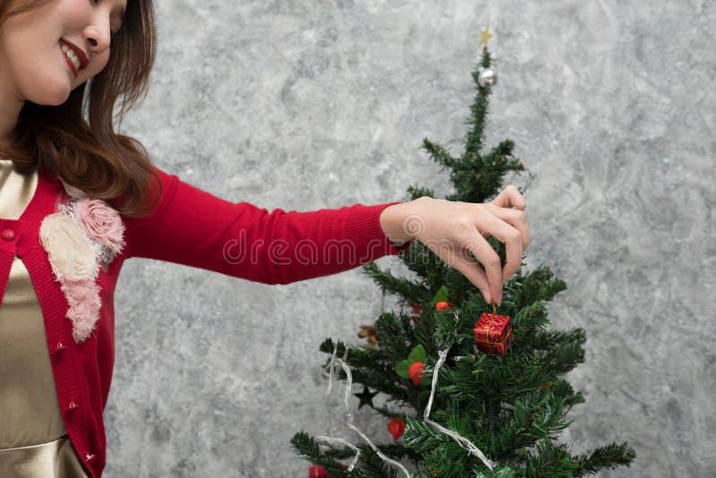 Frau, die Weihnachtsverzierung hält Mädchen verzieren Weihnachtsbaum in einem h lizenzfreies stockbild
