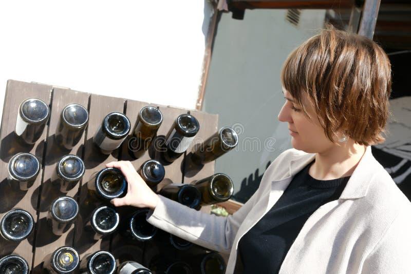 Frau, die Weinflasche ber?hrt stockbilder