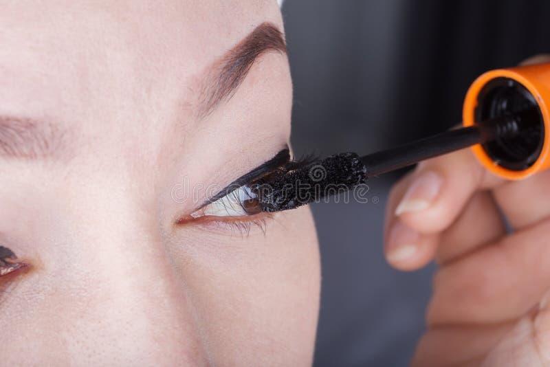 Frau, die Wimperntusche auf ihren Wimpern anwendet lizenzfreie stockfotografie