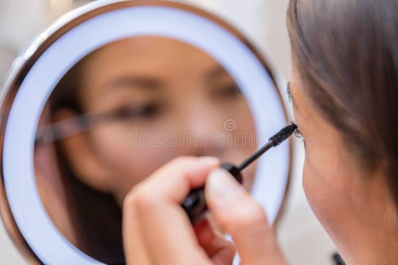 Frau, die Wimperntusche in beleuchteten Schminkspiegel einsetzt lizenzfreies stockfoto