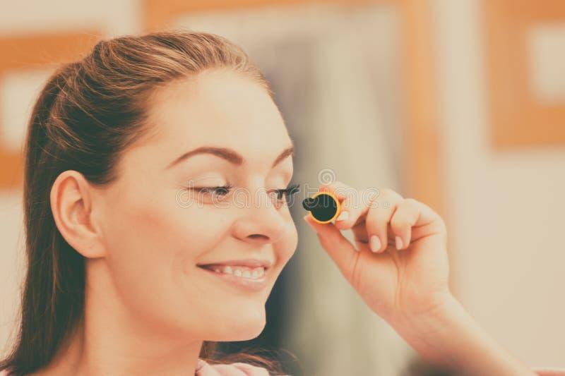 Frau, die Wimperntusche des blauen Auges auf ihre Wimpern zutrifft lizenzfreie stockbilder