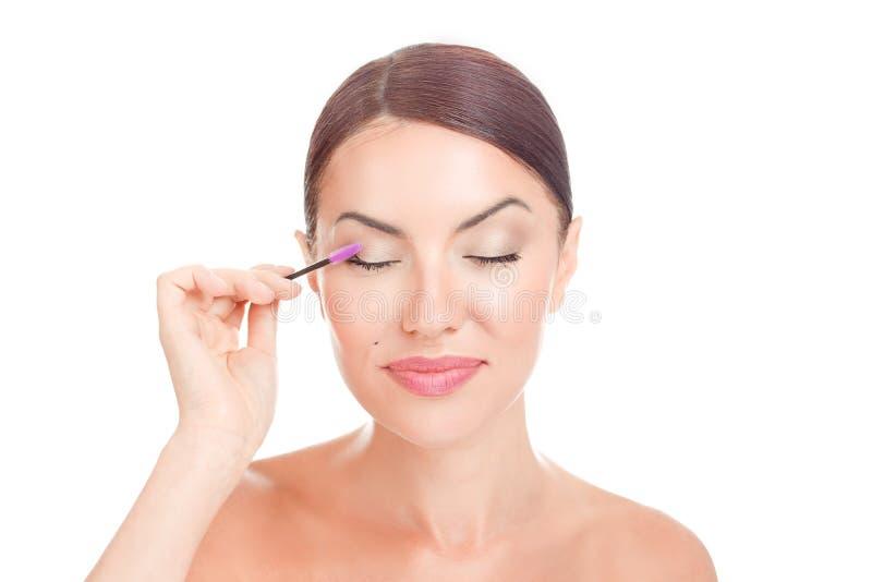 Frau, die Wimperserumätherisches öl auf Wimpern mit Make-upwimperntuschenbürste aufträgt stockbild