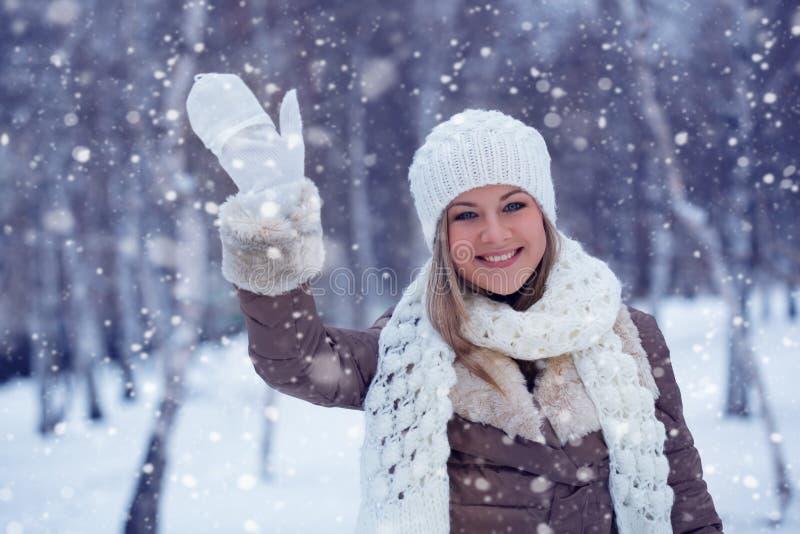 Frau, die in Winterpark wellenartig bewegt stockfotografie