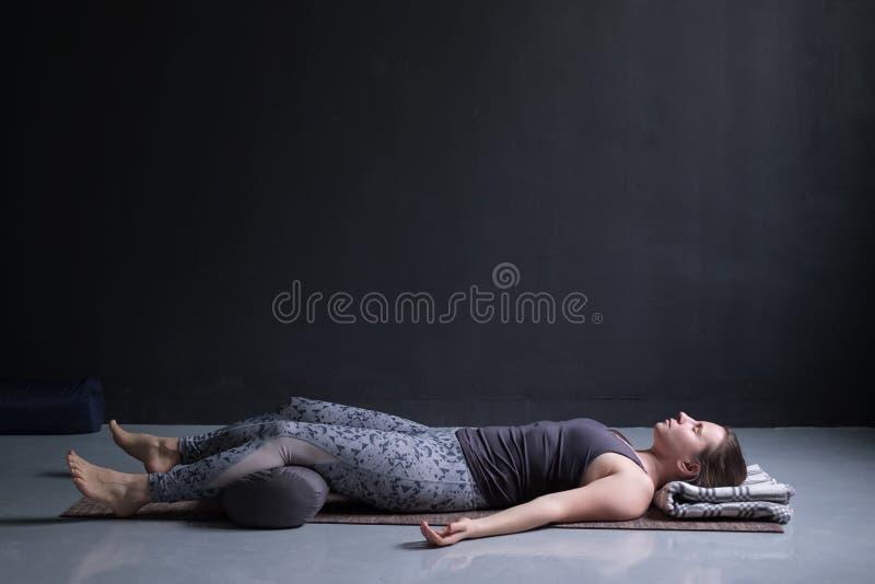 Frau, die, Yogaübung auf dem Bretterboden tuend ausarbeitet und liegen in Shavasana stockbilder