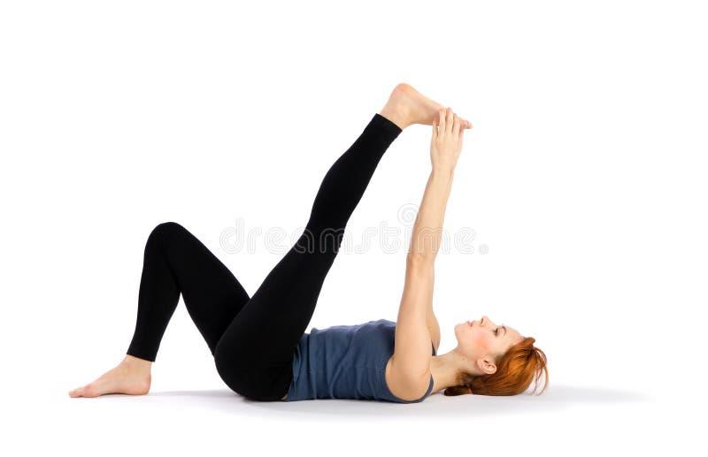 Frau, die Yoga-Übung ausdehnend tut stockbilder