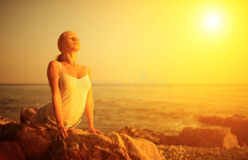 Frau, die Yoga auf dem Strand bei Sonnenuntergang tut stockbild
