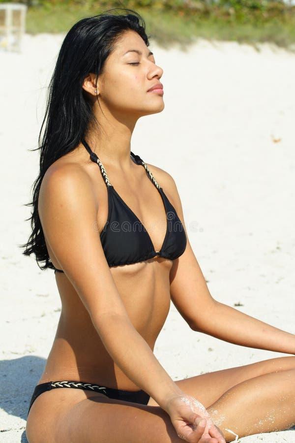 Frau, die Yoga auf dem Strand tut lizenzfreies stockfoto