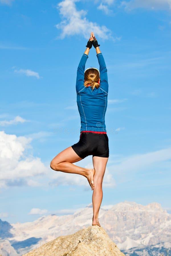Frau, die Yoga auf Felsen tut lizenzfreie stockfotografie