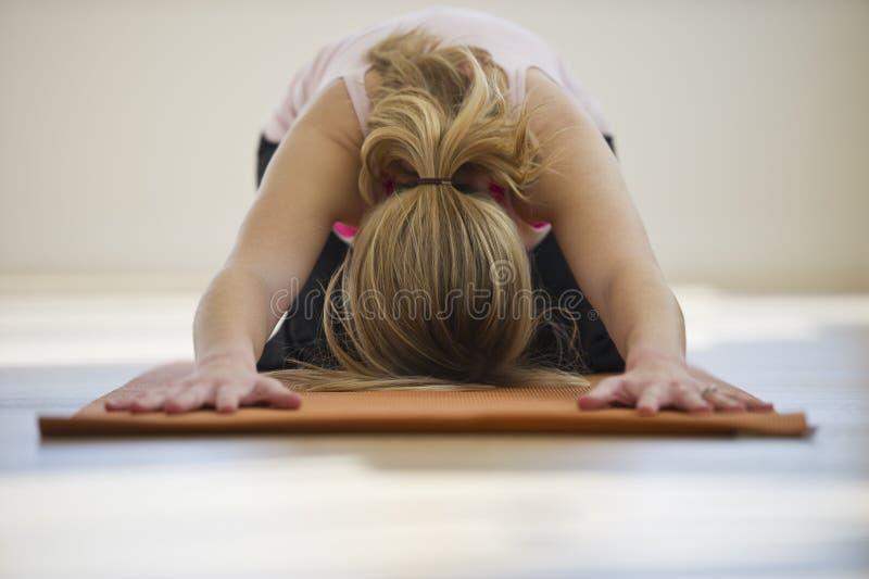 Frau, die Yoga auf Matte im Studio tut lizenzfreie stockfotografie