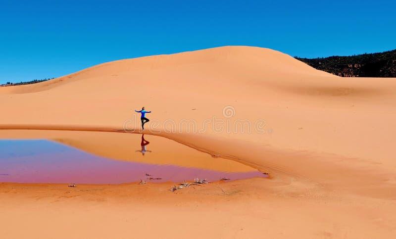 Frau, die Yoga auf Sanddünen tut lizenzfreie stockfotografie