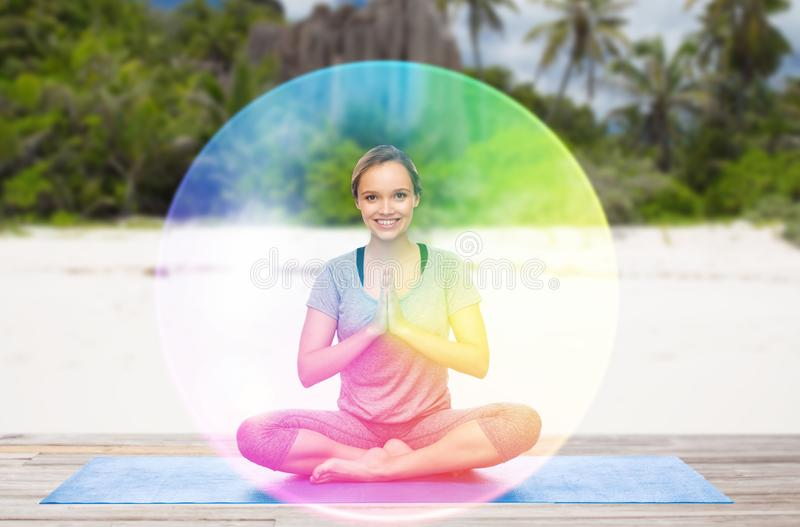 Frau, die Yoga in der Lotoshaltung mit Regenbogenaura tut stockfotos