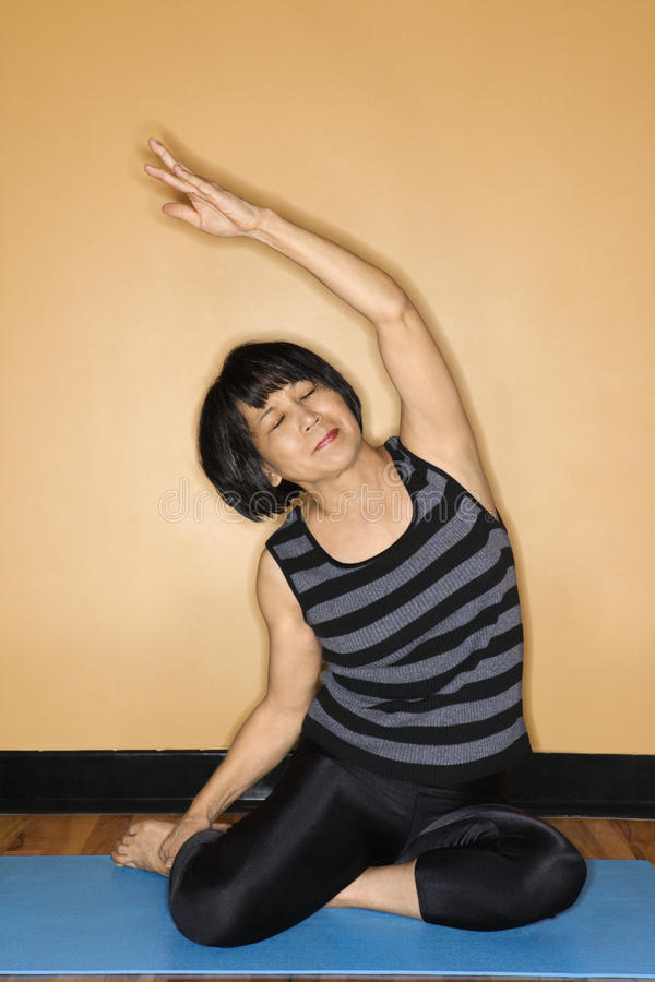 Frau, die in Yoga-Haltung ausdehnt lizenzfreies stockbild