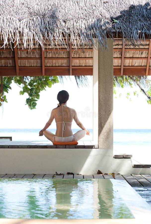 Frau, die Yoga im Maldives-Strandurlaubsort spielt lizenzfreies stockfoto