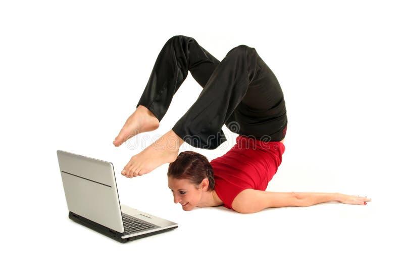 Frau, die Yoga mit Laptop tut stockfotografie