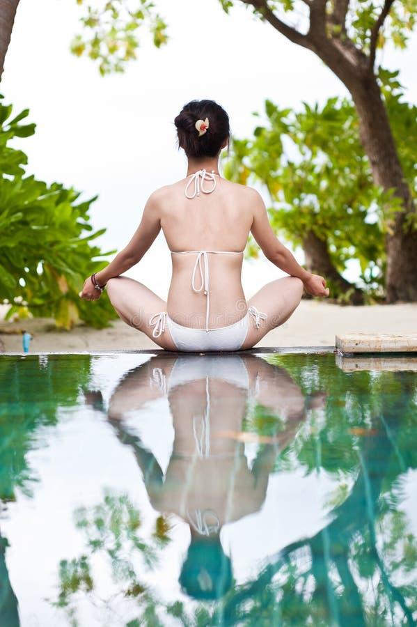 Frau, die Yoga neben dem Swimmingpool spielt lizenzfreie stockbilder