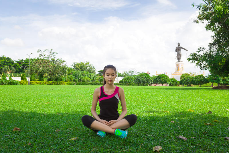 Frau, die Yoga am Park tut stockfotos