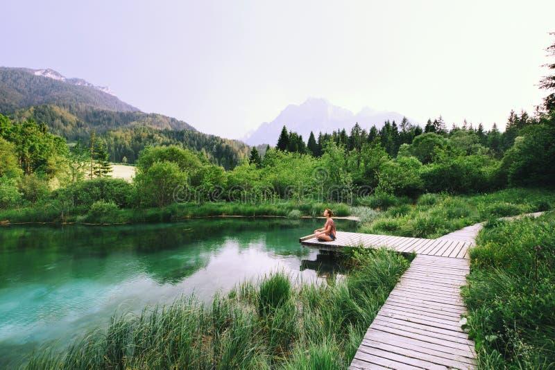 Frau, die Yoga tut und in Lotussitz auf der Natur meditiert stockfoto