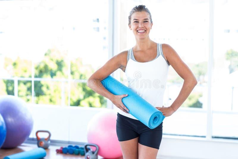 Frau, die Yogamatte mit der Hand auf Hüfte lächelt und hält stockbilder